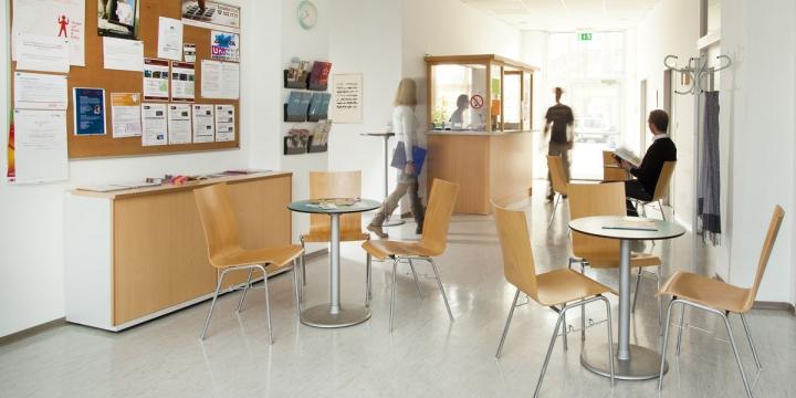 Beratungsstelle, Warteraum im Hintergrund verschwommene Personen die sich durch den Raum bewegen