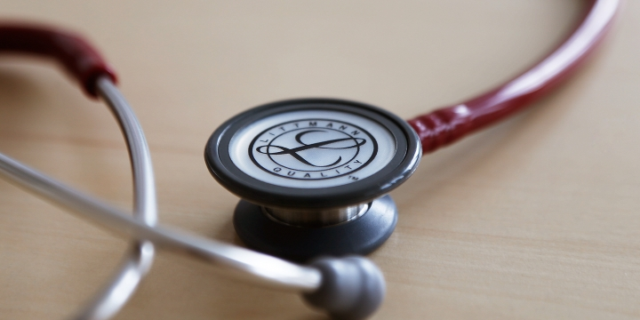 auf einem Tisch liegt ein zusammengerolltes Stetoskop