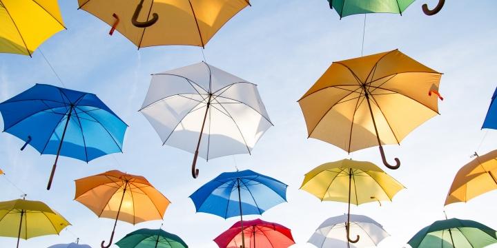 Bunte Regenschirme schweben vor blauem Himmel über den Betrachter