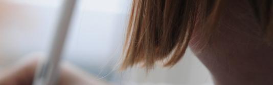 Detailaufnahme eines schreibenden Mädchens von hinten