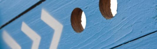 Blaue Holzwand mit Pfeilen, welche auf zwei Gucklöcher weisen