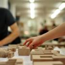 Hand versetzt Holzklotz auf einem Tisch in einer Werkstatt