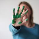Frau mit grüner Farbe auf Hand mit abweisender Handhaltung
