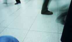 Ein Flur mit Ausschnitten von Beinen mehrerer Menschen in Bewegung