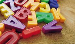 Verschiedene bunte Buchstaben aus Plastik auf einer Holzfläche