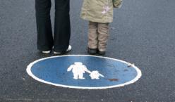 Beine von Elternteil und Kind vor einem blauen Verkehrszeichen