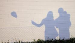 Schatten von Vater, Mutter und Kind mit einem Luftabllon an einer Mauer