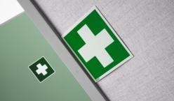 Schild mit grünem Kreuz auf Wand