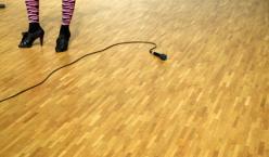 Beine auf Bühne mit frei am Boden liegenden Mikrofon