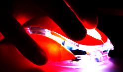 Hand auf Computer Maus in rotem Licht