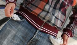 Mann zeigt die leeren Hosentaschen einer Jean