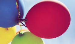 Bunte Luftballone fliegen in einen blauen Himmel