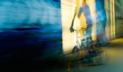 Radfahrer wird undeutlich und verschwommen vor einer beleuchteten Auslage dargestellt