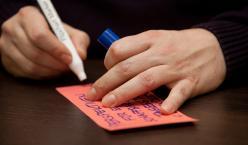 Stift in einer Hand, welche gerade auf eine Moderationskarte schreibt