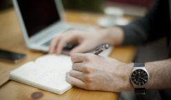 Männerhand mit Uhr schreibt in Notizbuch