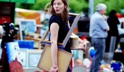 Junge Frau am Flohmarkt mit Bilderrahmen